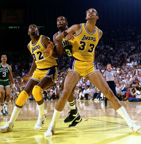LOS ANGELES - 1984: Magic Johnson #32 and Kareem Abdul Jabbar of the Los Angeles Lakers wait for a rebound during a game against the Boston Celtics at the Forum in Los Angeles, California. NOTE TO USER: User expressly acknowledges and agrees that, by downloading and or using this photograph, User is consenting to the terms and conditions of the Getty Images License Agreement. (Photo by Andrew D. Bernstein./ NBAE/ Getty Images)